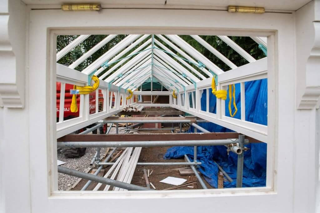 A picture looking through the timber frames of the glasshouses.