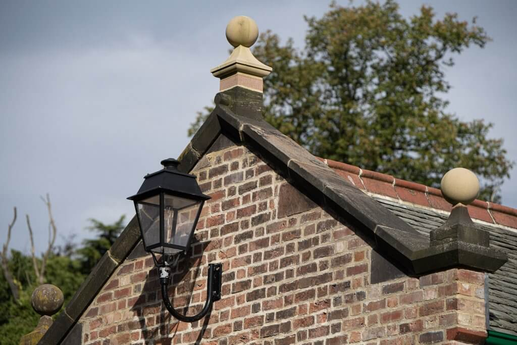 Old carriage lamp mounted on the side of the shippon buildings