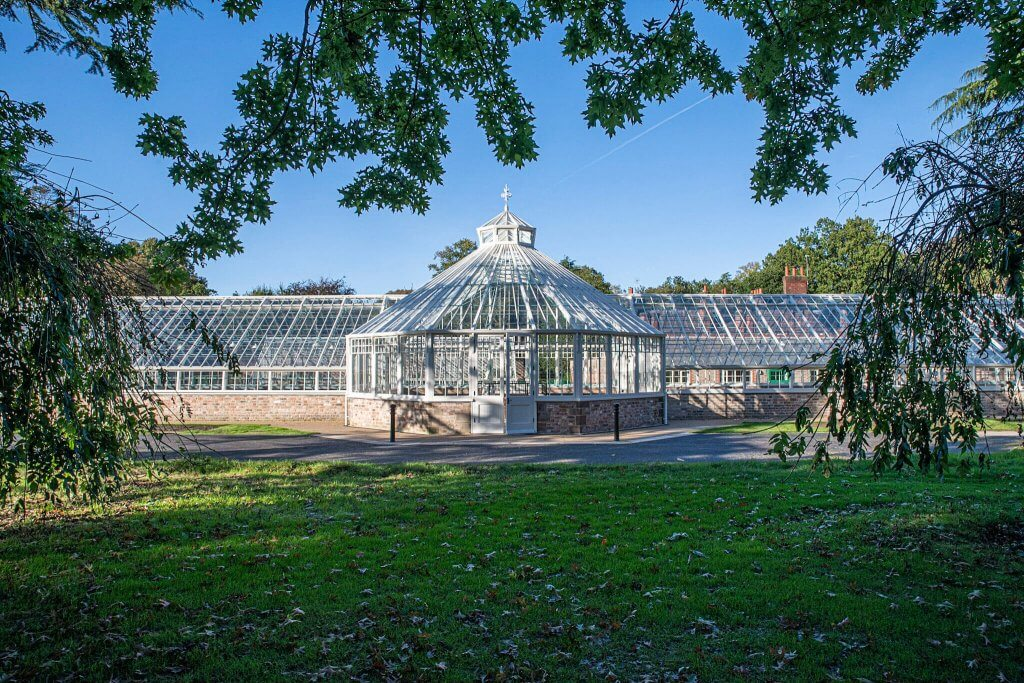 The glasshouses seen from across the lawns at Walton Hall and Gardens