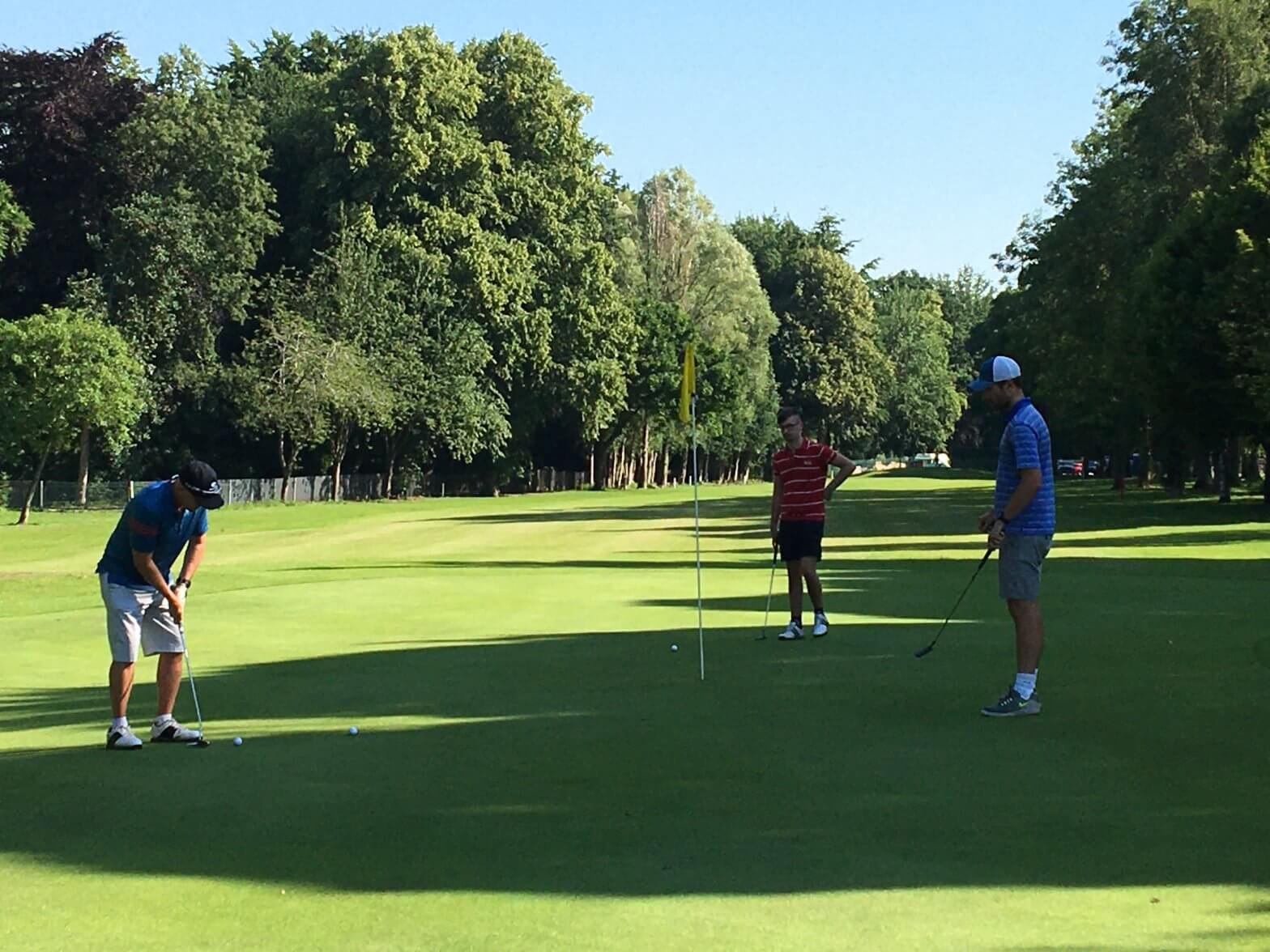 Three men on the green at Walton Hall Golf Course